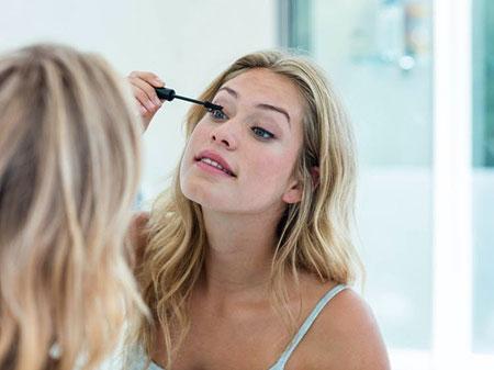 vrouw doet mascara op